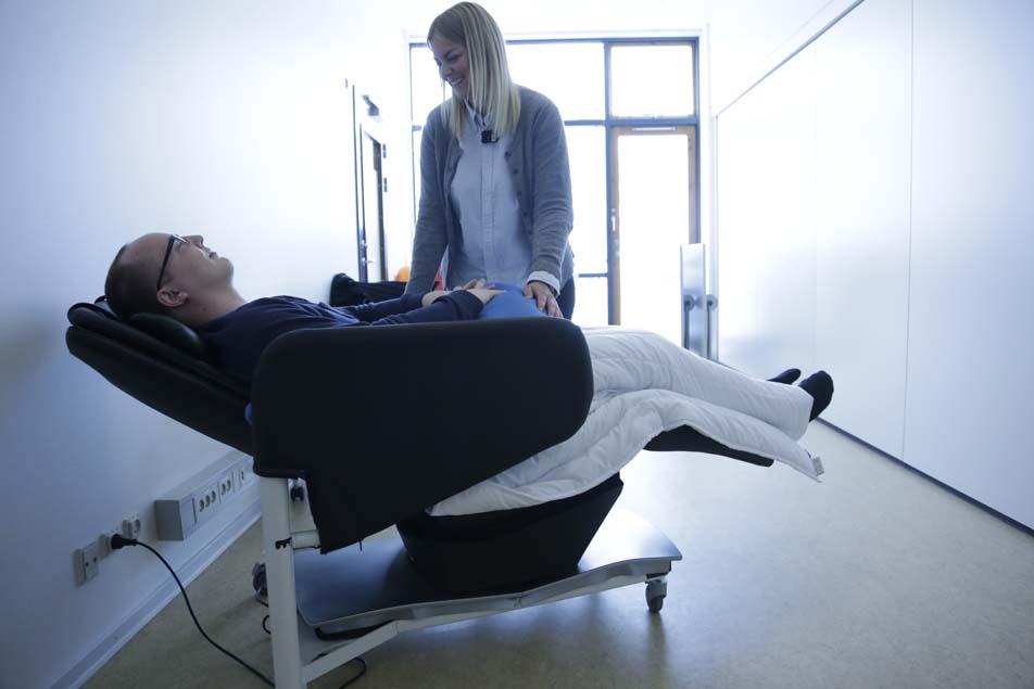 Andreas i vippestolen. Når patienterne sidder i den, får de et tyngdetæppe over knæene, mens en specialdesignet pude omslutter overkroppen. Som en båd i svag bølgegang vipper stolen frem og tilbage – til tonerne af afslappende musik.
