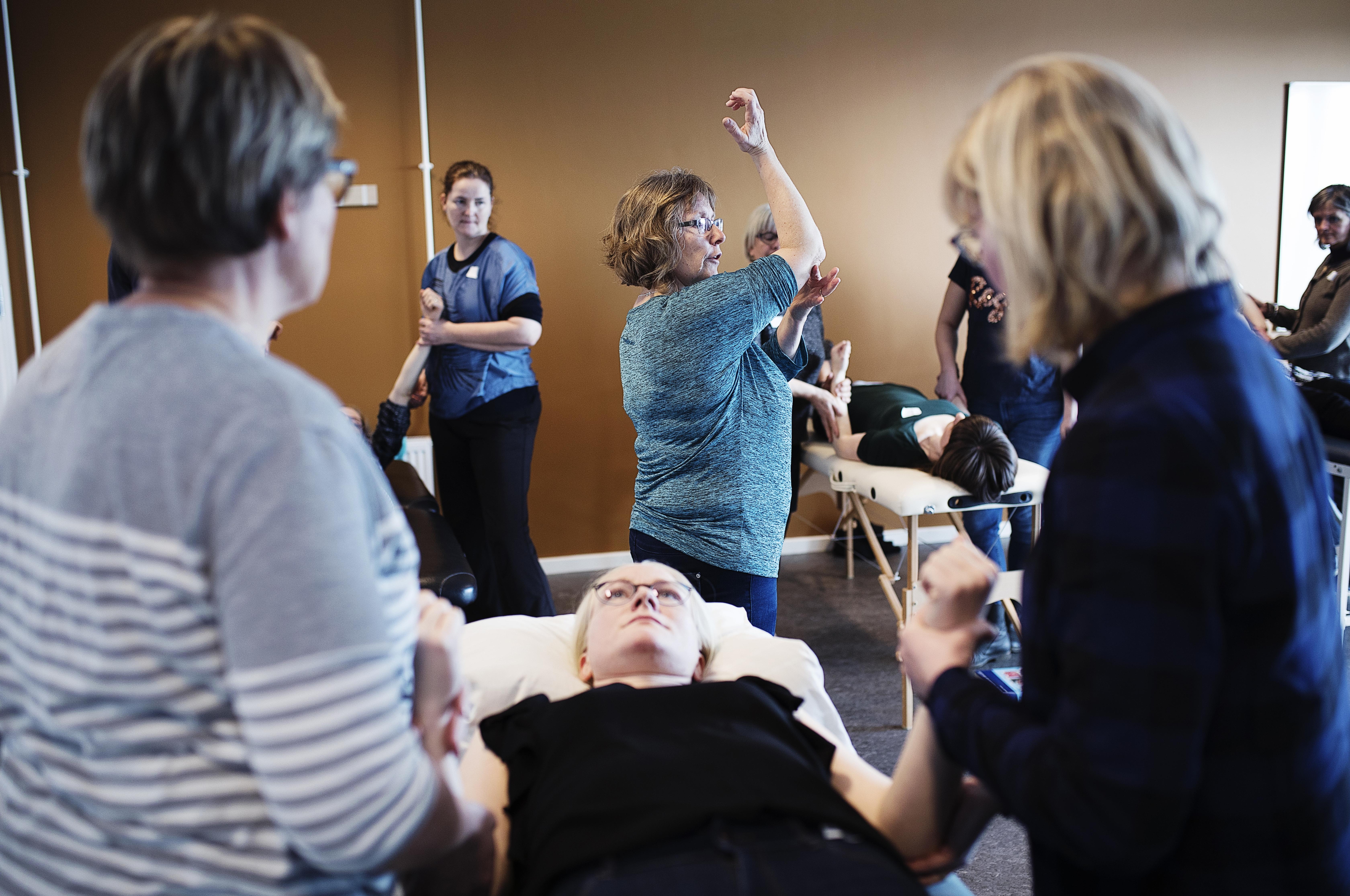 Fysioterapeut Elizabeth Lykholt Andreasen viser, hvor kursisterne kan mærke epicondylerne i albuen. Flere fortæller, at det er rart, at der er så god tid til de forskellige øvelser.