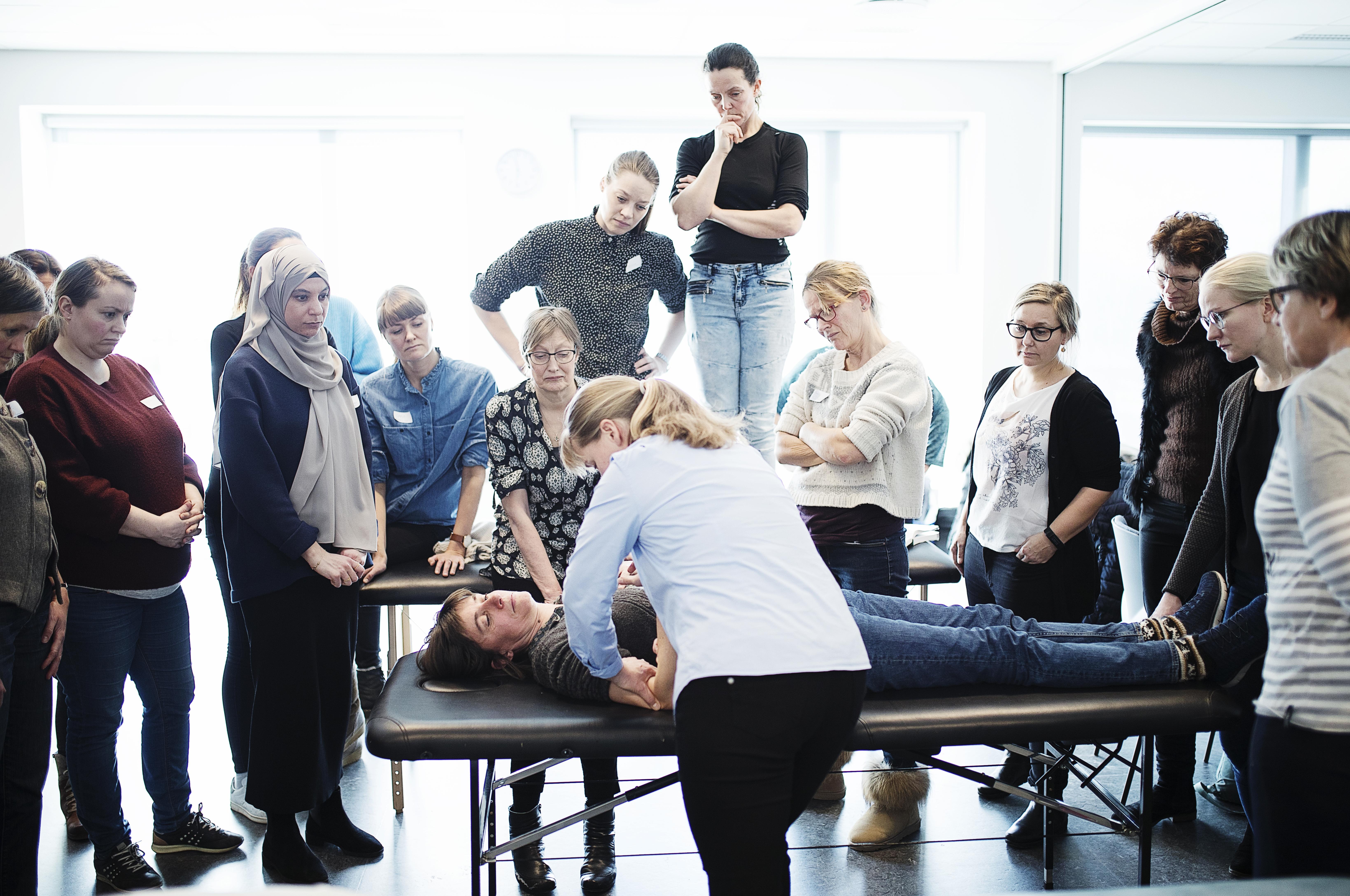 - Jeg skal bruge et offer, meddeler underviser Lotte Mejlvig Nielsen. Hun viser kursisterne, hvordan de laver et lille træk på ledkapslen, hvilket kan virke smertelindrende.