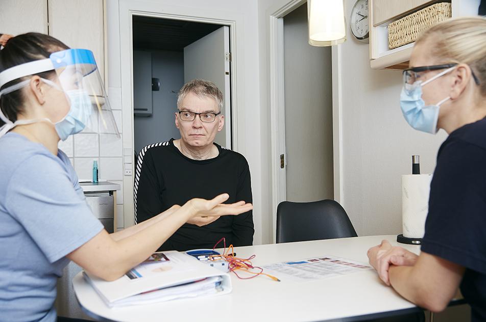 Ergoterapeuterne Linda-Maria Delgado Grove og Astrid Helene Daugård snakker med Henrik Jørgensen, der på grund af ALS har svært ved at styre tungen, hvilket påvirker både talen og spise- og synkefunktionen.