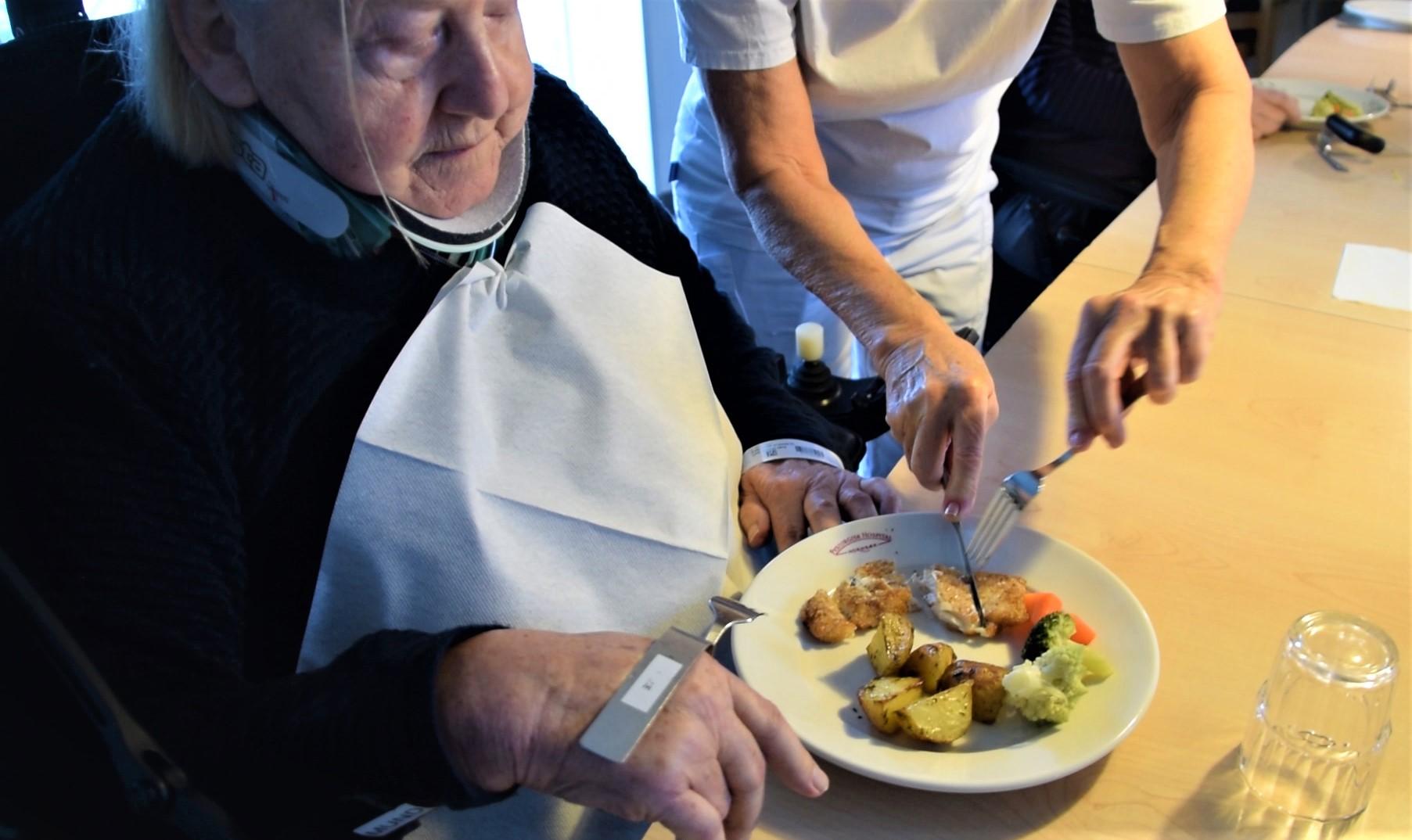Ergoterapeut Inge Steen skærer Signe Ilsøes mad i mindre stykker, giver hende en speciallavet ske og justerer hendes siddestilling. Justeringer, der er vigtige for, at hun kan lykkes med at spise selv med hjælp fra armstøtten.